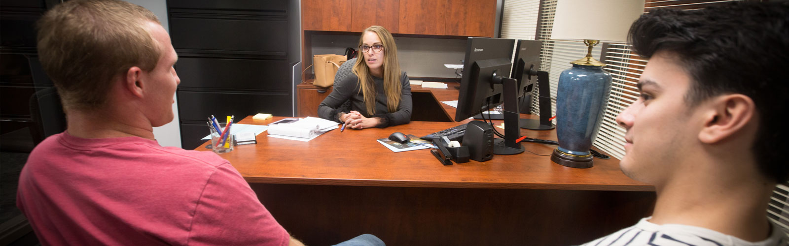 Law Professor speaking with two students in office setting