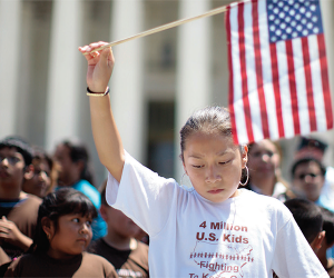 A girl holds a US flag in a crowd of children